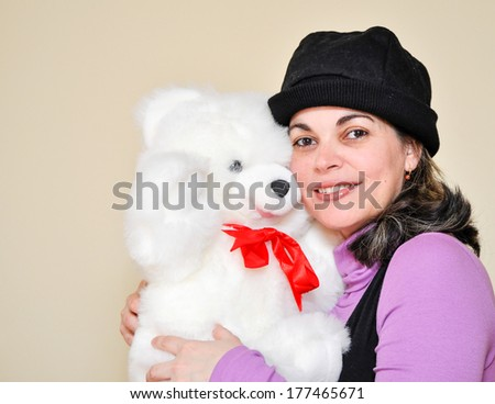 A mature woma still loves her childhood teddy bear - stock photo