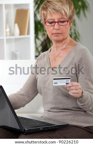 A mature woman doing online shopping. - stock photo