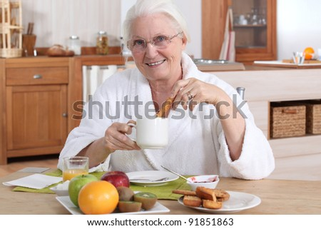A mature woman having breakfast. - stock photo