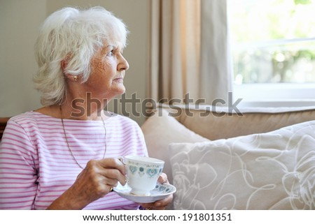 A mature woman  holding a cup and saucer while looking out the window with copyspace - stock photo
