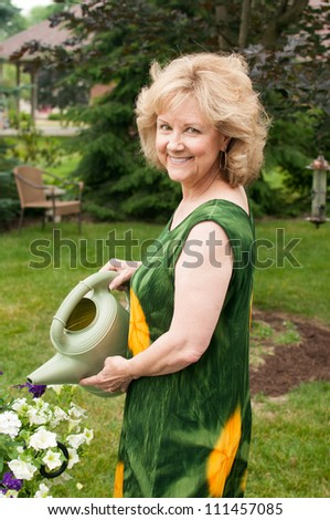 A mature woman holds a watering can - stock photo