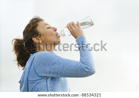 A mature woman in her forties wearing a blue hooded top and drinking from a bottle of water.