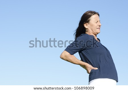 A mature woman in pain, obviously suffering from back problems, with a stressful facial expression, clear blue sky as background and copy space. - stock photo