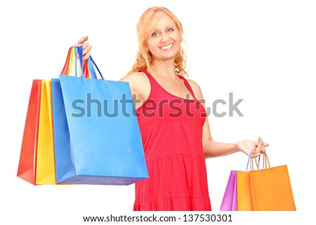 A mature woman posing with shopping bags isolated on white background