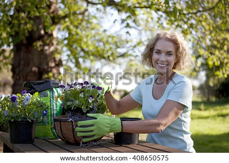 A mature woman sitting at a garden bench planting hanging baskets - stock photo