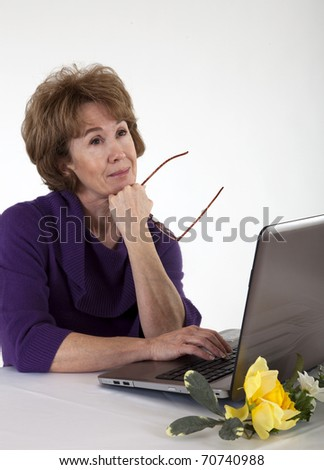 A mature woman sitting in front of her laptop computer with a dreamy sort of expression on her face. - stock photo