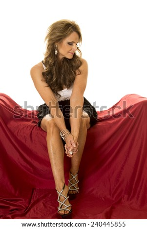 a mature woman sitting on her couch in her formal dress. - stock photo