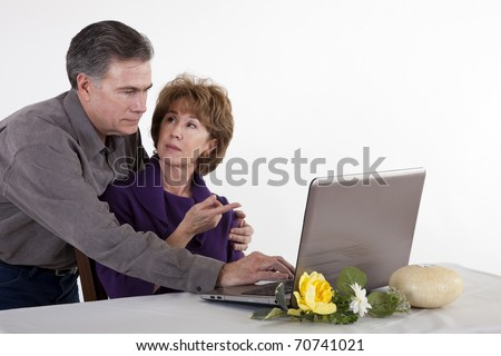 A mature woman with a puzzled look on her face being assisted with her computer by her husband.