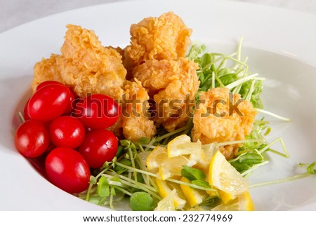 A meal of fried shrimp and cherry tomatoes - stock photo
