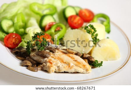 A meal of marinaded, grilled chicken breast with mushrooms, salad and potato.