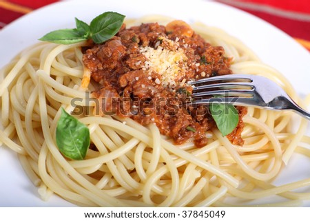 A meal of spaghetti bolognese garnished with basil leaves - stock photo