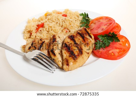A meal of spicy grilled cajun chicken breasts with vegetable rice and fresh tomato - stock photo