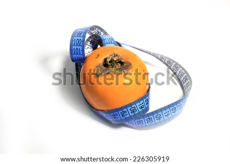 a measuring  ribbon and ripe tropical fruit is a persimmon - stock photo