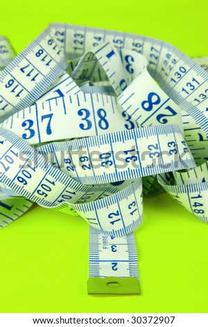 A measuring tape isolated against a lime green background
