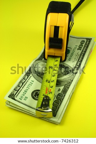 a measuring tape over bills of one hundred dollars - stock photo