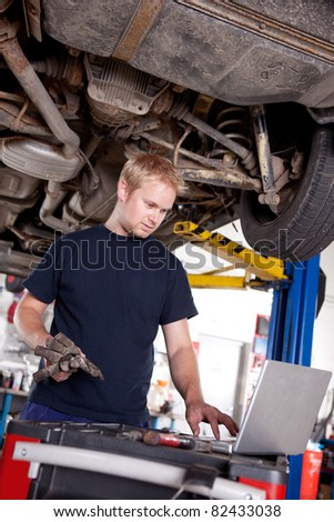 A mechanic in a garage looking at a laptop - stock photo