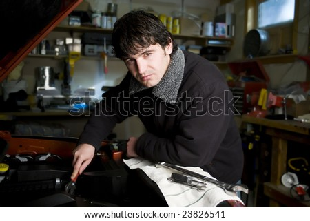 A mechanic in his workshop working on a vehicle engine - stock photo