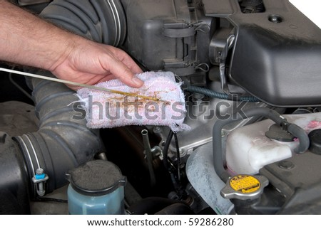 A mechanic inspects the level of oil on a car engine dipstick. - stock photo