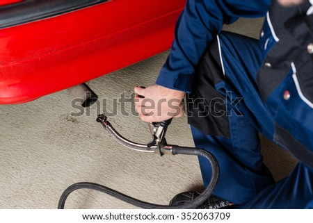 A mechanic is applying a diagnostic sensor to the ehaust of a red car, measuring the composition and substances in the exhaust fumes in a garage. - stock photo