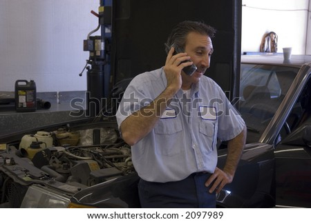 a mechanic is on the phone giving a customer some information - stock photo