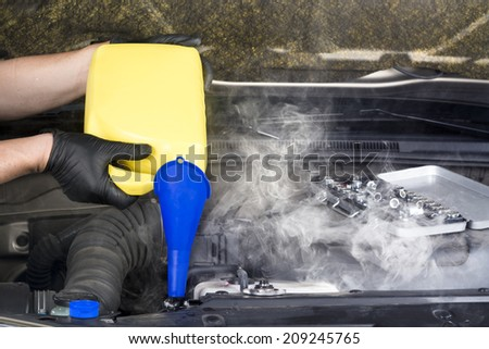 A mechanic pours engine coolant into an overheated automobile radiator in an attempt to cool it down and stop the steam.