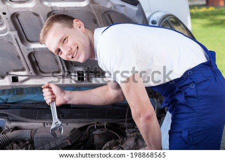 A mechanic repairing a car and smiling - stock photo