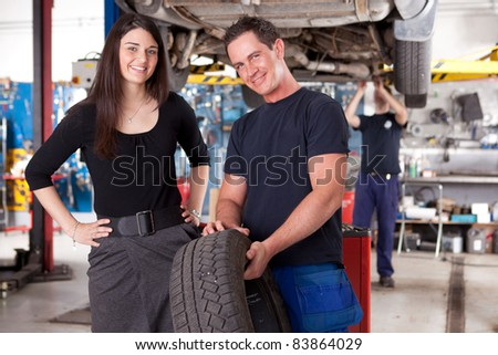 A mechanic showing a tire to a happy female customer - stock photo