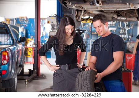 A mechanic showing the tread of a tire to a female customer - stock photo