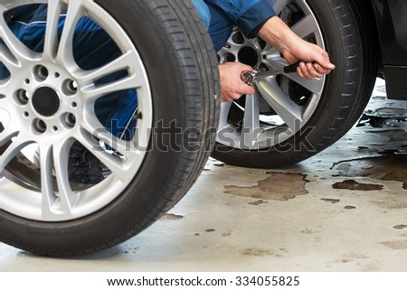 A mechanic tightening the wheel nuts on an alloy light weight rim after having exchanged summer tires for winter tires - stock photo