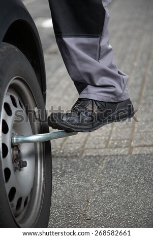 A mechanic tries to unscrew the tire screws with the foot to do a tire change. - stock photo