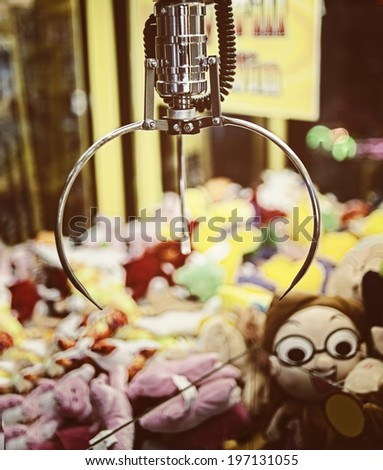 A mechanical arm selecting a random soft toy in a vending machine. - stock photo