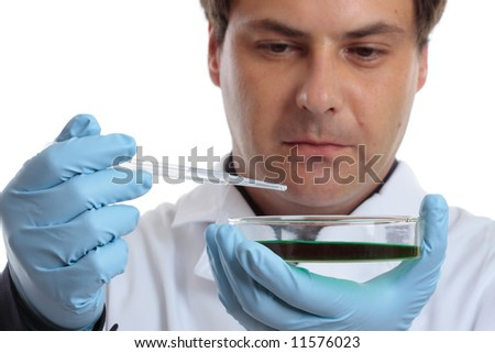 A medical or agricultural scientist, chemist or researcher holding a petri dish and pipet with clear fluid.  Focus to dish and hands not the man
