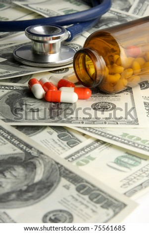 A medical stethoscope and pills on dollars - stock photo