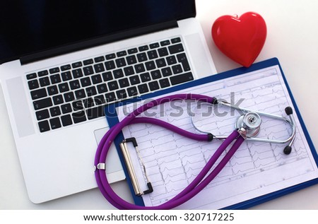 A medical stethoscope near a laptop on a table, on white - stock photo