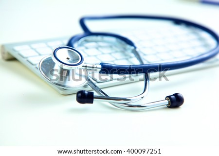 A medical stethoscope near a laptop on table, on white - stock photo