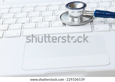 A medical stethoscope on a laptop - stock photo