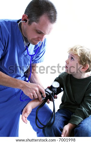 A medical worker taking a young boy's blood pressure - stock photo