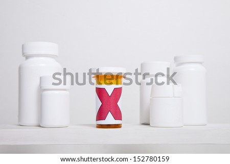 A medicine bottle with a large red cross sits on a shelf with white bottles. - stock photo