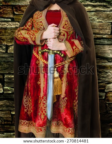 A Medieval Female Joan of Arc Warrior with Sword at Castle Wall - stock photo