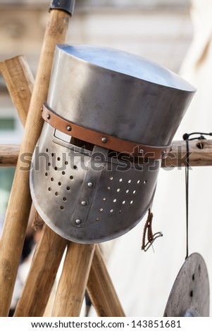 a medieval knight's helmet on a wooden pole - stock photo