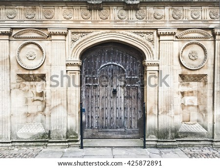 A medieval wooden door in a red brick wall - stock photo