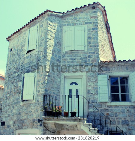 A mediterranean stone medieval house with doorway, steps, window shutters and pot plants (Budva, Montenegro). - stock photo