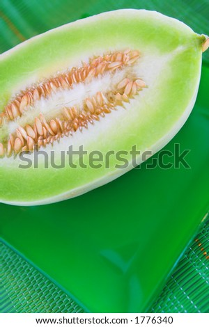 A melon cut in half on a green plate and placemat. - stock photo