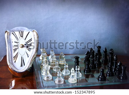 A melting and distorted Dali clock and a chessboard with a game in progress - stock photo