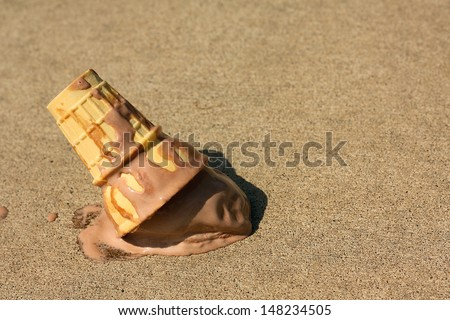 A melting chocolate ice cream cone has dropped upsidedown onto the sidewalk on a sunny summer day - stock photo