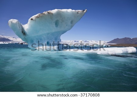 A melting glacial iceberg floating on the Iceberg Lagoon, Jokulsarlon, Iceland the drips of melt water can be seen coming off the iceberg. - stock photo