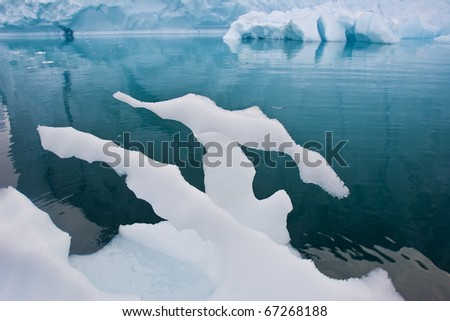 a melting piece of ice floating along the frozen coasts of greenland - stock photo