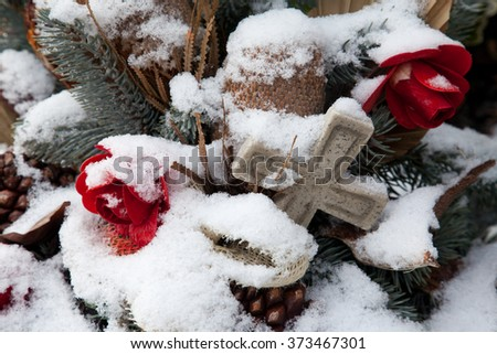 A memorial with a crucifix and flowers in winter - stock photo