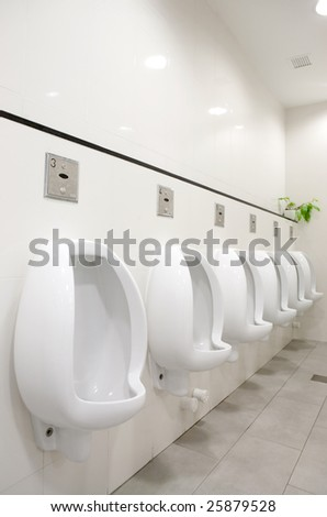 A mens public bathroom with urninals on the wall - stock photo