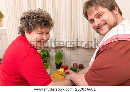 a mentally disabled woman and a young man cooking together - stock photo